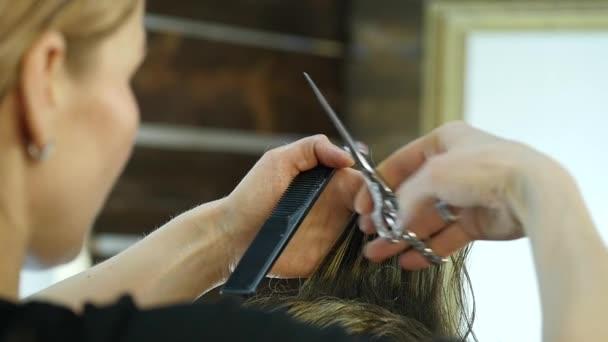 Tvarování pánské stříhání ženské kadeřník používá nůžky v salónu krásy. Zpomalený pohyb