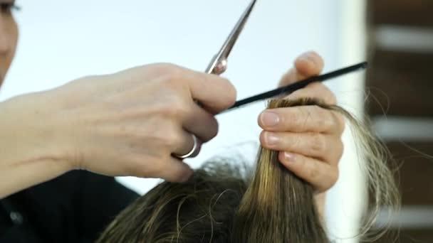 holiči ruce používá nůžky pro tvarování Pánské vlasy v salónu krásy. Zpomalený pohyb