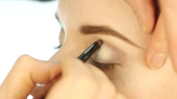 Eye makeup woman applying eyeshadow powder. Stylist is doing make up for female by eyeliner. slow motion