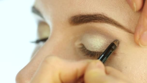 Eye makeup woman applying eyeshadow powder. Stylist is doing make up for female by eyeliner. 4K