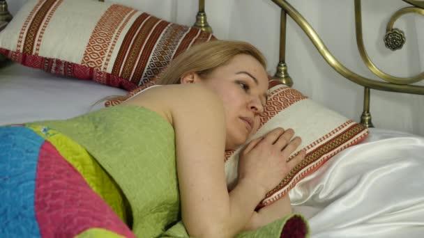 Szőke nő felébred, ébresztőóra néz, és elrejti azt a párnája alá. 4k
