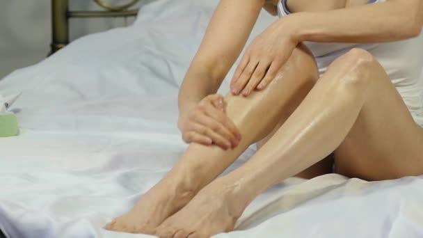 женщина, применяя крем на ноги. ноги концепция ухода кожи ...