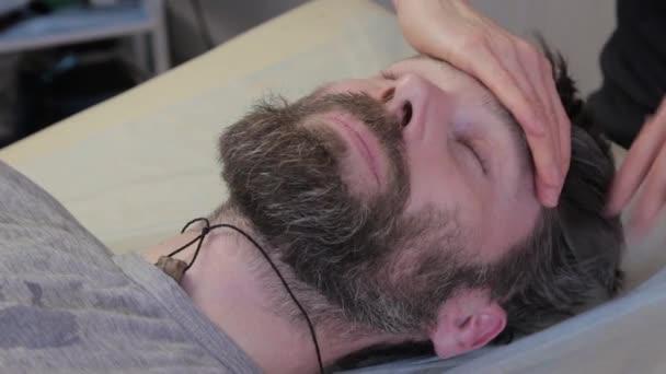 Muž dostává masáž obličeje. kosmetický zákrok, prevence stárnutí kůže. leží v kanceláři kasmetologa