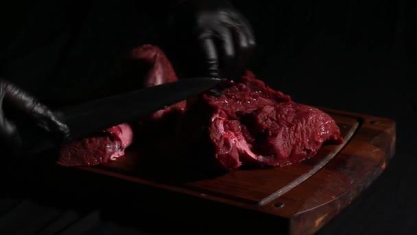 Der Koch bereitet das Fleisch zum Braten zu. Fleischerhände schneiden Fleischscheiben mit dem Messer