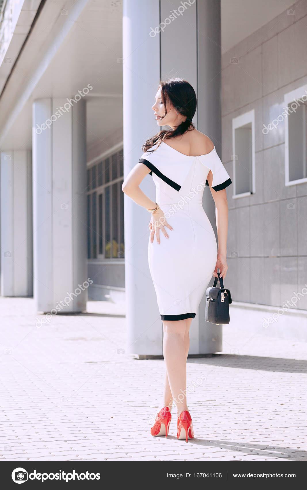 283b7b02f9ac Giovane bella ragazza elegante in vestito bianco e borsa nera. a piedi e  posa all aperto. stile di moda