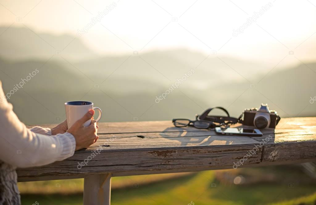 Woman drinking coffee in sun sitting outdoor in sunshine light enjoying her morning coffee, vintage,