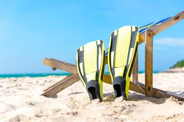 Summer Day.  Yellow diving fins laying on the beach, during sunny summer day, blue sky background. Travel and Summer Concept