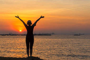 Silhouette women runner listening music and feeling freedom, happy and enjoying nature sunset.  Lifestyle and Healthy Concept.