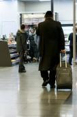 Aeroporto di chassid. Ebreo ortodosso con una valigia sta andando intorno allaeroporto