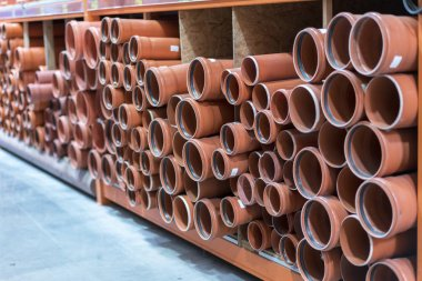 Sewer pipes in the building store. KG sewer pipes. Stacks of PVC and ceramic water pipes