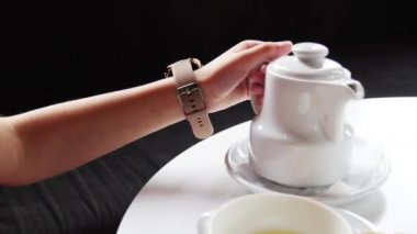 Girl pours tea in a cup. tea Maker.A cup of tea
