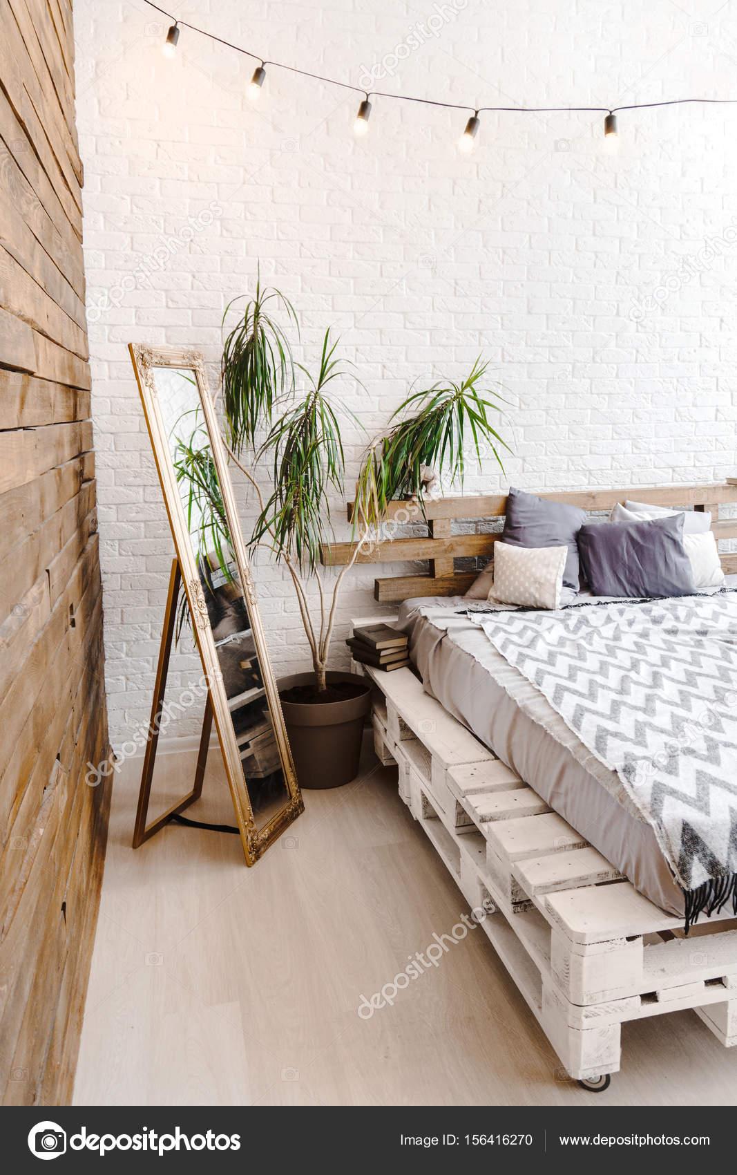 kreativstudio weißen innenraum mit paletten-bett, spiegel und lampen