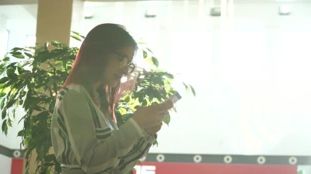 Žena využívání mobilního telefonu v nákupní centrum