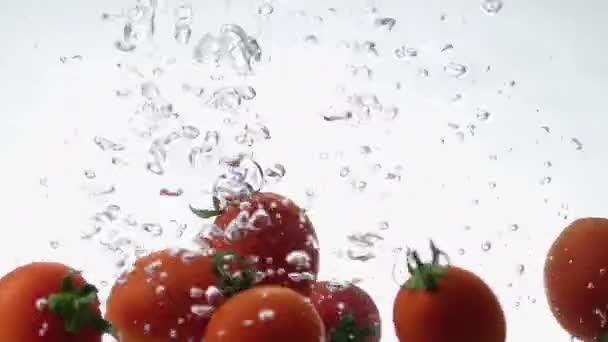 Großaufnahme von frischen und gesunden Kirschtomaten, die in klares Wasser fallen, mit großem Spritzer auf weißem Hintergrund. 3 Clips in einer Einstellung für Ihre Projekte