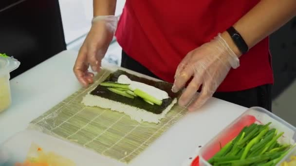 Asian master cooking sushi. A man in transparent gloves skillfully make rolls on a mat of bamboo or makisu on white table in the kitchen. Rolls with rice and cucumber prepare for sale and eat.