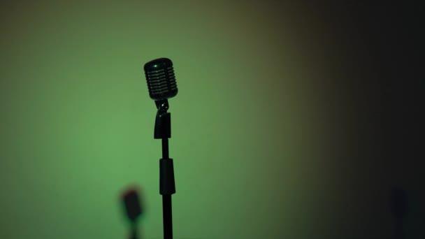 Professzionális koncert vintage mikrofon rögzítésére vagy beszélni közönség standon sötét üres retro klub. A kék reflektorfény fénye másodpercenként villog egy króm mikrofonon, zöld alapon..