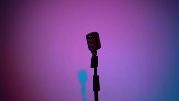 Professzionális vintage vakító mikrofon rögzítésére vagy beszélni a színpadon sötét üres retro klub közeli. Spotlights ragyog a króm mikrofon közepén több színű háttér. Közeledik a kamera..