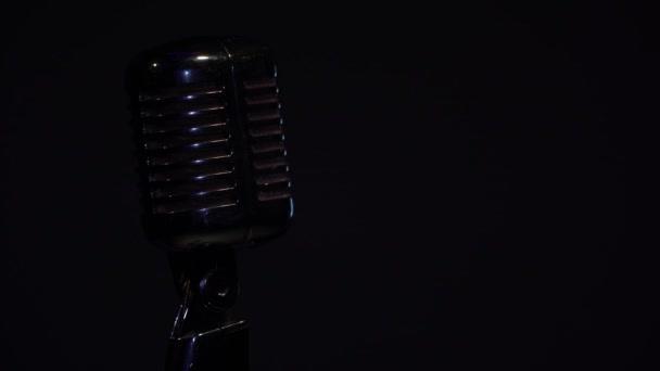 Kialszik a villany. Professzionális koncert vintage glare mikrofon rekord vagy beszélni közönség a színpadon sötét üres retro klub közeli. Spotlight kikapcsolja a fekete háttér.
