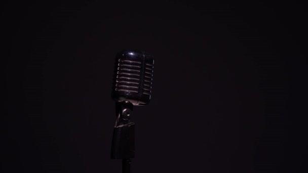 Professzionális koncert vintage vakító mikrofon rögzítésére vagy beszélni közönség a színpadon sötét üres térben közeli. Piros, fehér és zöld reflektorok ragyognak króm retro mikrofon fekete alapon.