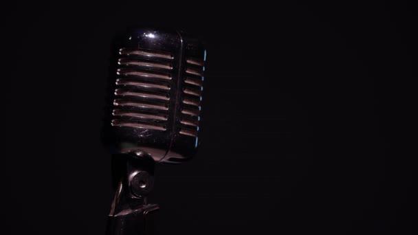 Metallic koncert vintage glare mikrofon rögzítésére vagy beszélni közönség a színpadon sötét üres klub közeli. Piros reflektorfény megvilágítja a króm retro mikrofon fekete alapon.