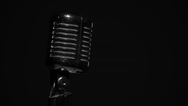 Professzionális koncert vintage vakító mikrofon rögzítésére vagy beszélni közönség a színpadon sötét üres térben közeli. Fehér reflektorok ragyog egy króm retro mikrofon a bal oldalon a fekete háttér.