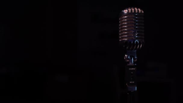 Professional concert vintage glare microphone for record or speak to audience on stage in dark empty space close up. Spotlights shine on a chrome retro mic on the right on black background.