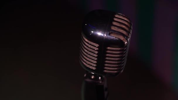 Kilátás felülről ezüst retro vakító mikrofon rögzítésére, vagy beszéljen a helyszínen sötét üres klub közeli. Spotlights ragyog egy króm retro mikrofon kiemeli a fekete háttér. Felülnézet.