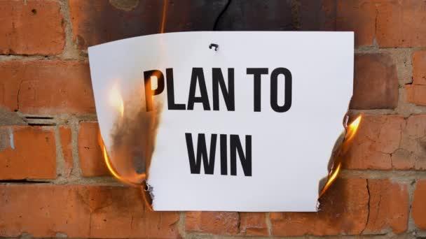 Nápis na bílém listu formátu A4 na pozadí oranžové cihlové zdi. Papír s černým slovem Plán na výhru hoří, kouří a mění se v popel. Obchodní koncept.