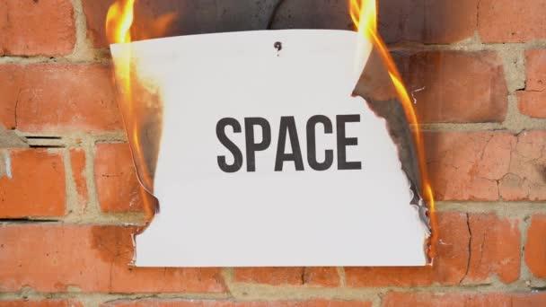 Nápis na bílém listu formátu A4 na pozadí oranžové cihlové zdi. Papír s černým vesmírem hoří, kouří a mění se v popel. Obchodní koncept.