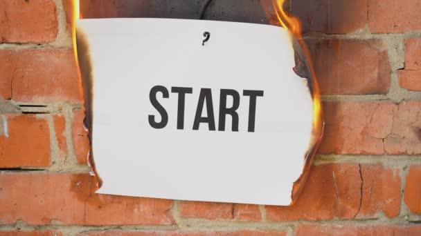 Nápis na bílém listu formátu A4 na pozadí oranžové cihlové zdi. Papír s černým slovem Začněte hořet, kouřit a změňte se v popel. Obchodní koncept.