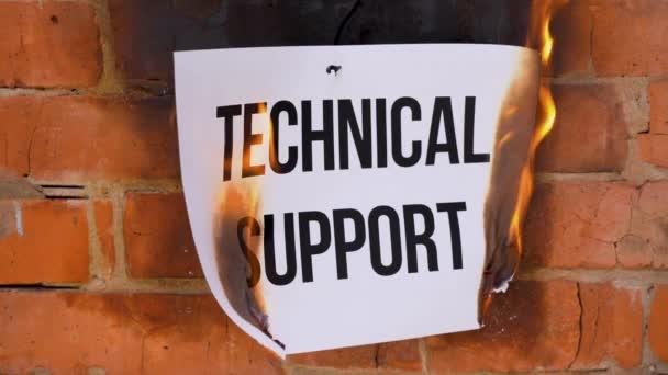 Nápis na bílém listu formátu A4 na pozadí oranžové cihlové zdi. Papír s černým slovem Technická podpora hoří, kouří a mění se v popel. Obchodní koncept.