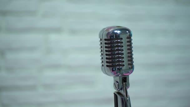 Professzionális koncert ezüst vintage vakító mikrofon a színpad jobb oldalán, retro klub közeli. Spotlight ragyog egy króm retro mikrofon a helyszínen egy fehér homályos háttér.