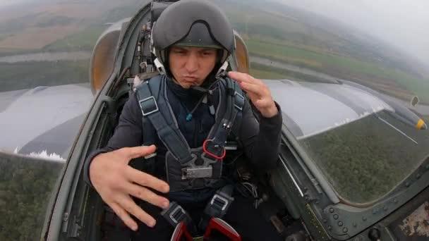 Flugschüler sitzt zum ersten Mal im Flugzeug. Der Mensch ist glücklich und tanzt. Vorbereitung eines neuen Piloten für Flüge im Flugzeug. graues Kampfflugzeug am Himmel. Innenansicht aus dem Cockpit aus nächster Nähe.