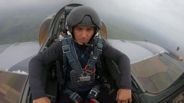 Bělošský krasavec v navigátoru helmy pilota. Muž se uvolní a dělá gesta koza nebo rocker. Šedé bojové stíhací letadlo letící nad polem a řekou. Vnitřní pohled zblízka z kokpitu.