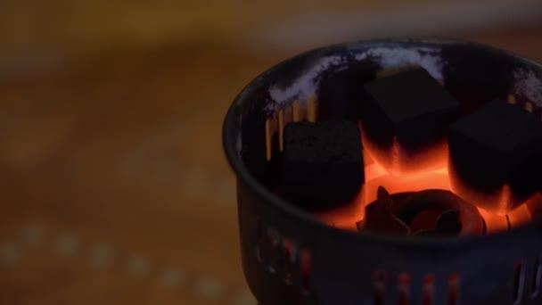 In einem alten speziellen elektrischen Campingbrenner werden Kohlen entzündet. 3 schwarze quadratische Kohlen kochen und erwärmen sich von der heißen Temperatur auf einer glühenden Spirale auf der rechten Seite vor einem verschwommenen dunklen Hintergrund Nahaufnahme.