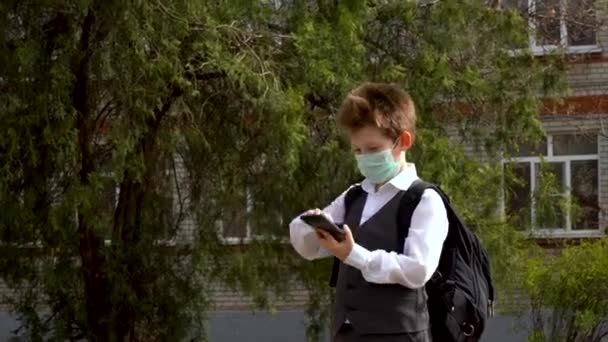 Little attractive boy in white shirt and gray suit in protective guard mask answer a call, speak by phone on sunny day against background of green tree and brick building with windows outdoor.