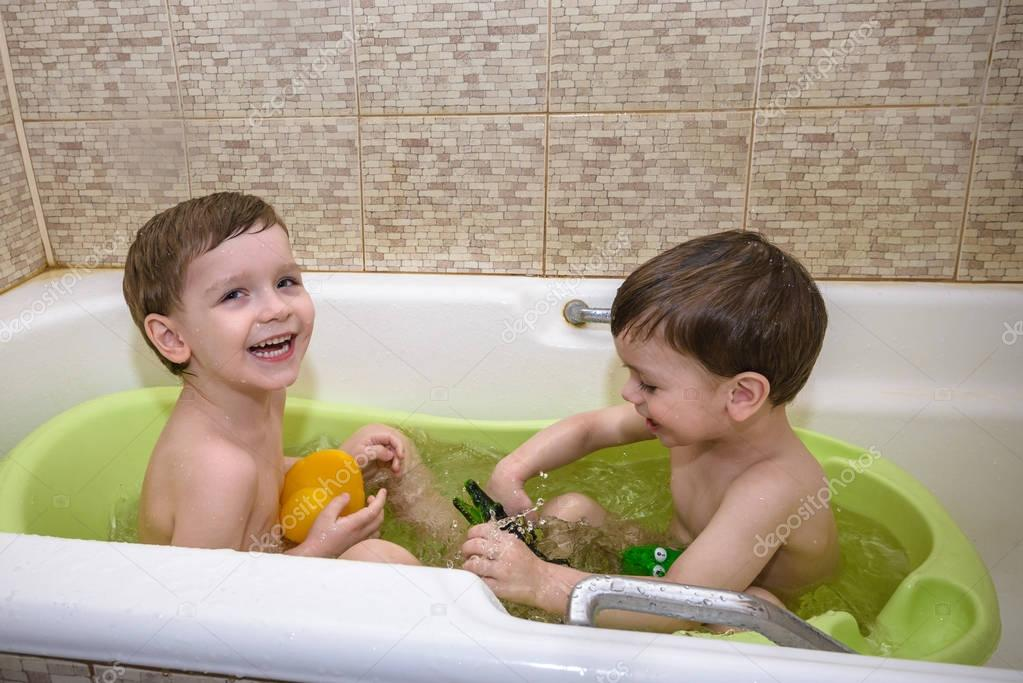 Two little twins children playing together with water by taking bath ...
