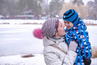 happy woman and kid embracing under winter snow