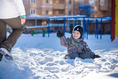 Boy jumping in snow. Happy kid walking outdoors in winter city. Child smiling and having fun.