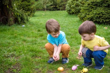 Kids on Easter egg hunt in blooming spring garden. Children searching for colorful eggs in flower meadow. Toddler boy and his brother friend kid  play outdoors