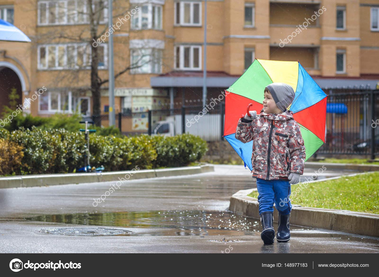 Ragazzino che gioca nel parco estate piovosa bambino con for Piani di fattoria sotto 2000 piedi quadrati