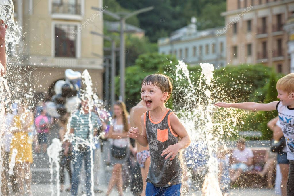 KYIV, UKRAINE AUGUST 13, 2017: Happy kids have fun playing in city water fountain on hot summer day.