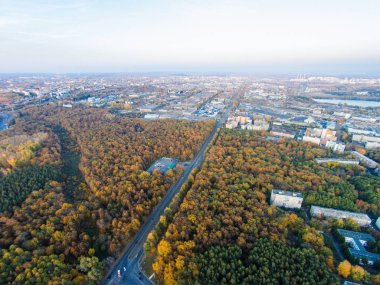 Autumn in city. Panoramic aerial view at road, forest, lake