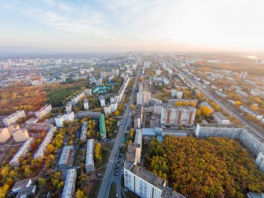 Autumn in city. Panoramic aerial view at road, forest, river.