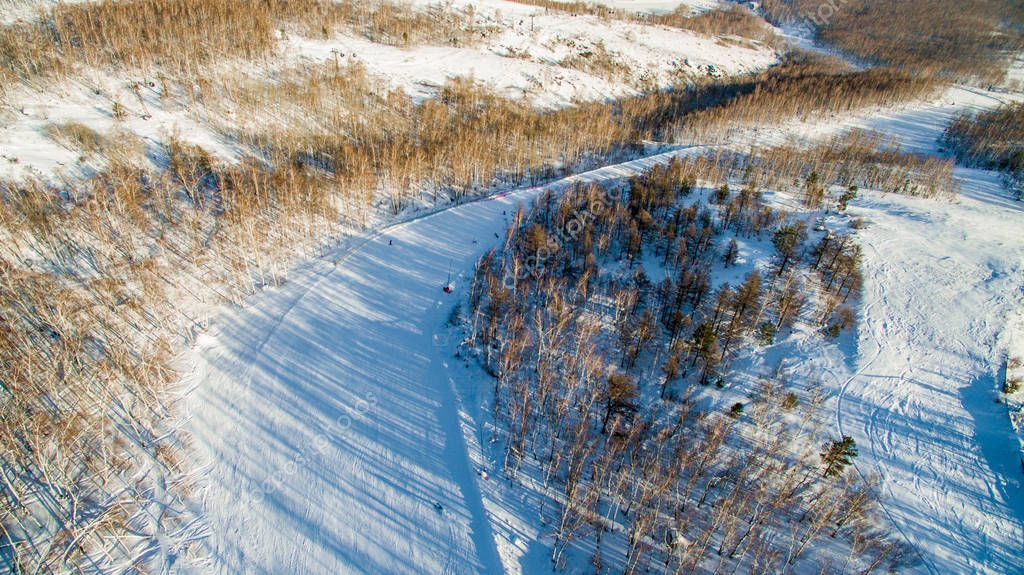 Skiers and snowboarders slide down mountainside near lake Bannoe. Aerial