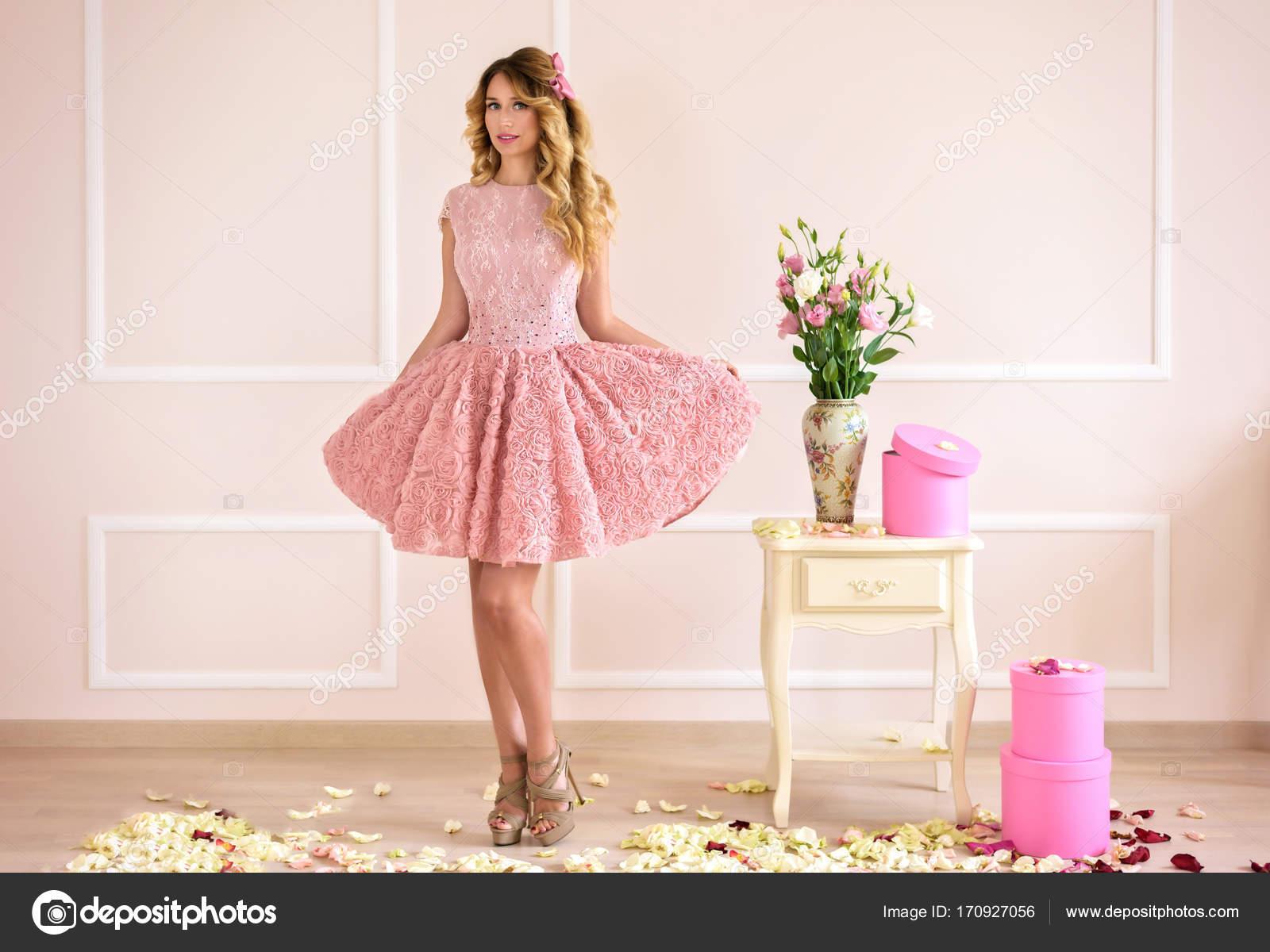 Feliz chica rubia y hermosa en un vestido rosa. Estilo de la muñeca ...