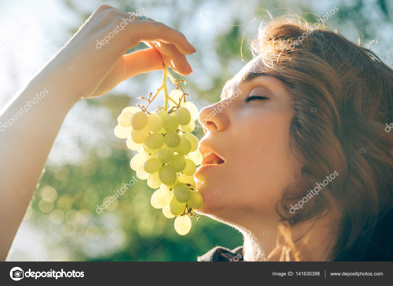 Portrait Of Young Beautiful Woman Holding Grapes Wants To