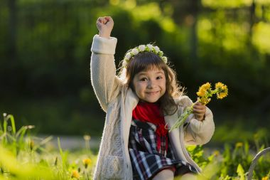 Cute young girl wearing wreath of dandelions and smiling while sitting on grass in park