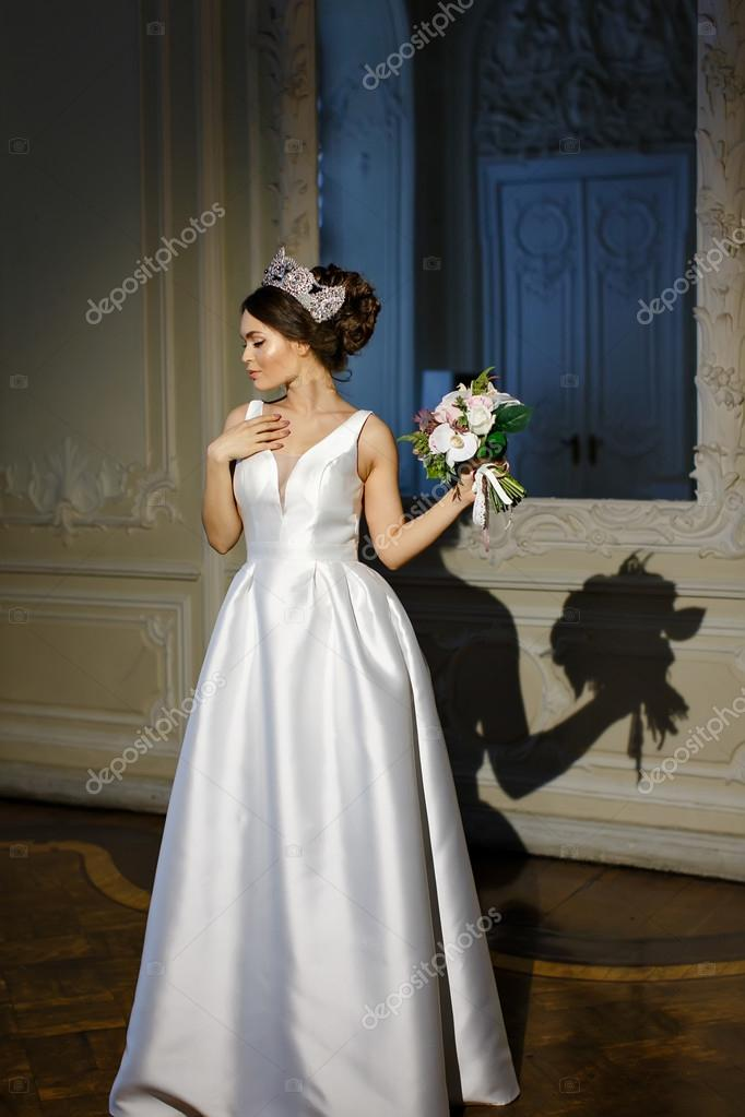 75105cc194 Piękna brunetka dziewczyna w białej sukni i genialny koroną na głowie we  wnętrzach pałacu — Zdjęcie od Coy Creek