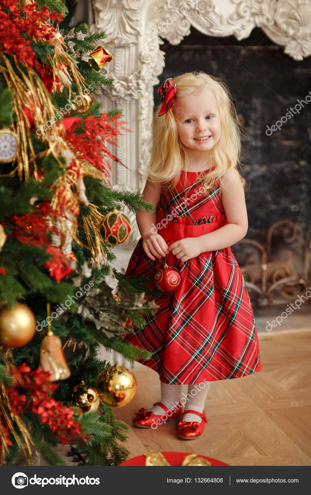 Girl baby blonde in a red dress next to the Christmas tree stand ...